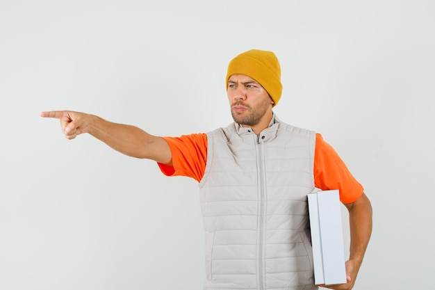 Tシャツ、ジャケット、帽子を背負って、段ボール箱を持って集中して見える若い男