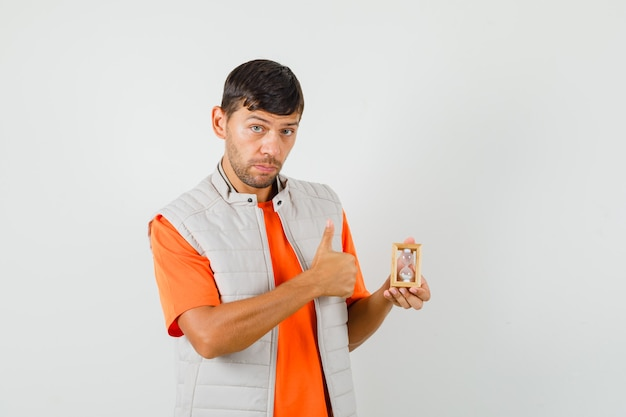 Tシャツ、砂時計を保持しているジャケット、親指を上に表示、正面図の若い男。