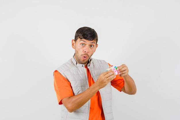 Молодой человек в футболке, куртке держит кубик рубика и выглядит удивленным, вид спереди.