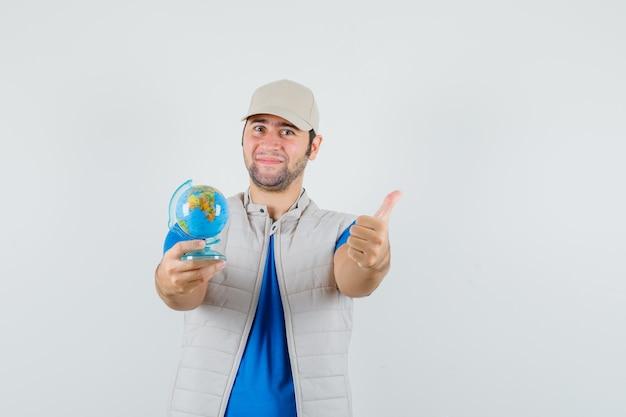 Tシャツを着た若い男、学校の地球儀を保持しているジャケット、親指を立てて陽気に見える、正面図。