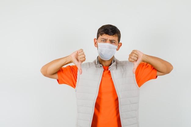 Tシャツ、ジャケット、マスクを着た若い男が二重の親指を下に向けて失望しているように見える、正面図。