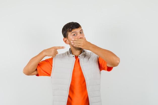 Молодой человек в футболке, куртка, указывая на его руку в рот, вид спереди.