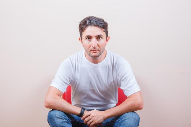 Молодой человек в футболке, джинсах сидит на стуле и выглядит озадаченным