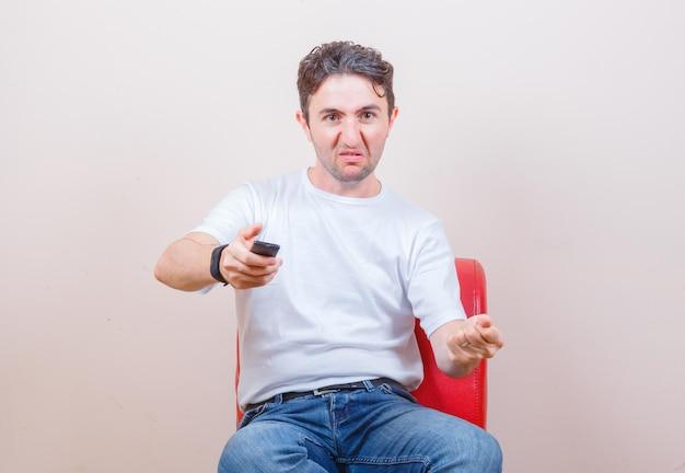 Молодой человек в футболке, джинсах использует пульт дистанционного управления, сидя на стуле и выглядит сердитым