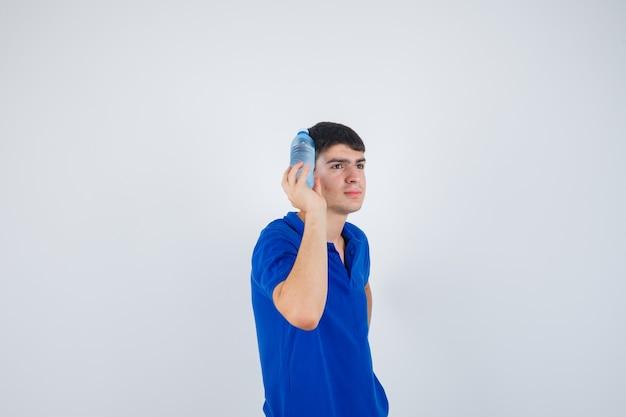 Молодой человек в футболке держит пластиковую бутылку возле головы и выглядит уверенно, вид спереди.