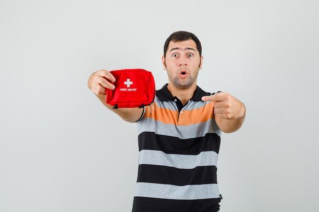 Молодой человек в футболке указывает на аптечку и выглядит изумленным