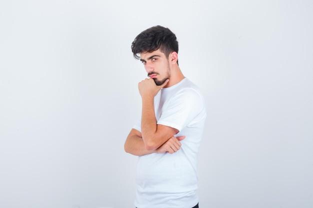 Молодой человек в футболке позирует, стоя и выглядит уверенно