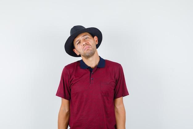티셔츠를 입은 젊은 남자가 얼굴을 찌푸리고 입술을 구부리고 무력해 보이는 앞모습.