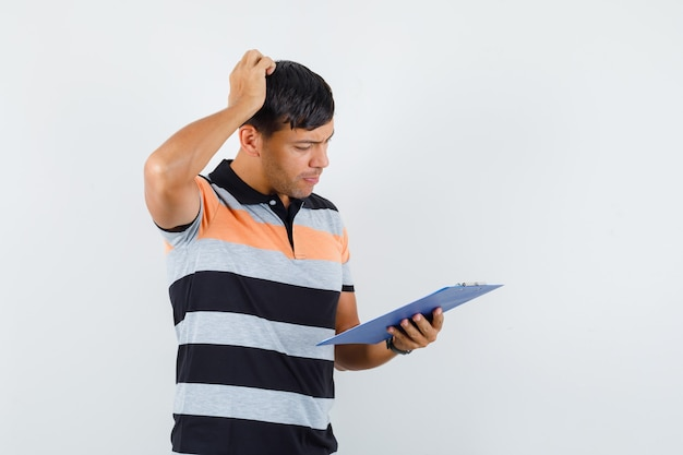クリップボードを見ながら物思いにふけるtシャツの若い男が頭を掻く
