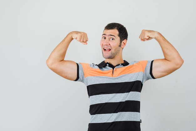 彼の腕の筋肉を示し、柔軟に見えるtシャツの若い男