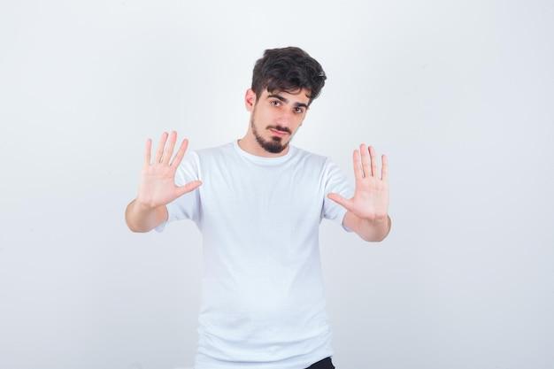 停止ジェスチャーを示し、怖がって見えるtシャツの若い男