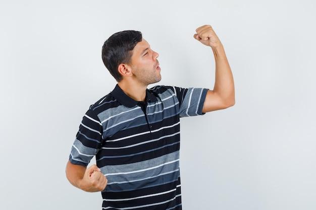 Молодой человек в футболке показывает жест победителя и выглядит удачливым, вид спереди.