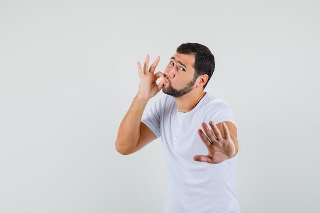 Молодой человек в футболке показывает жест на молнии, показывая знак остановки и выглядит обеспокоенным, вид спереди.