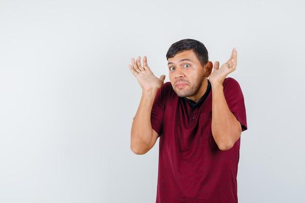 肩をすくめる、降伏ジェスチャーで手を上げて、怖がって見える、正面図のtシャツを着た若い男。