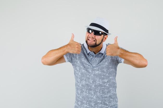 T- 셔츠, 엄지 손가락을 보여주는 선글라스와 만족, 전면보기에 젊은 남자.