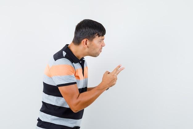 Молодой человек в футболке предупреждает кого-то пальцами и выглядит сердитым