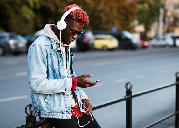 Молодой человек в городе смотрит на телефон