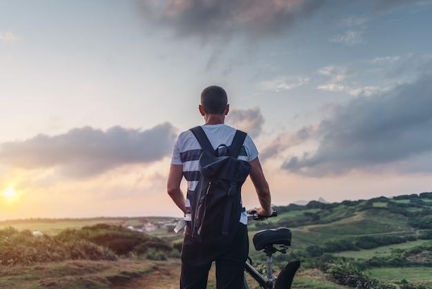 自転車で丘の上に立っている日没の夕方の若い男
