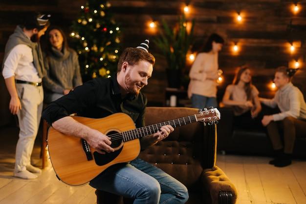Молодой человек в праздничной шляпе играет мелодию на гитаре на фоне разговоров друзей. рождественская елка с гирляндой и стеной с праздничным освещением в фоновом режиме.