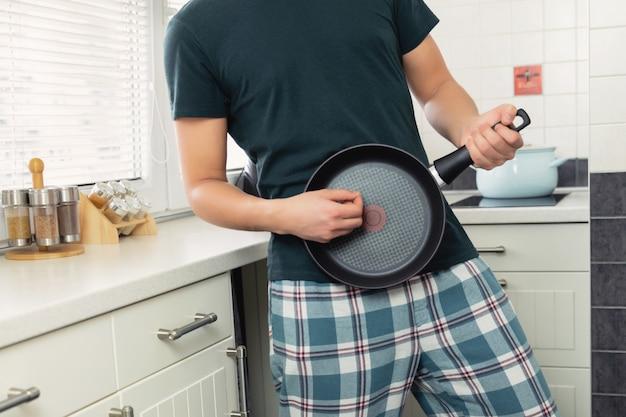 ギターのように鍋を滴下とキッチンで若い男。