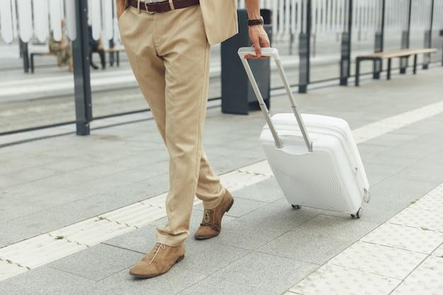 バス停で白いスーツケースを持って立っているトレンディなフォーマルな服装の若い男。屋外で公共交通機関を待っている男性観光客
