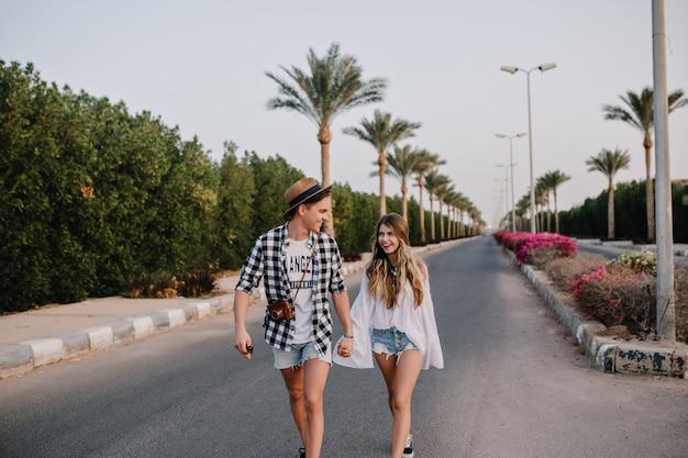 トレンディな帽子とデニムのショートパンツの若い男がガールフレンドの手を握って、脇に茂みがある通りを歩きます。外で時間を過ごすスタイリッシュな衣装の美しいカップルは、エキゾチックな景色を楽しんでいます