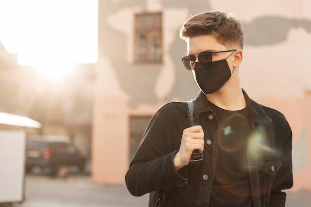 保護用の黒いマスクを着たデニムジャケットを着たトレンディなサングラスをかけた若い男が通りに立つ