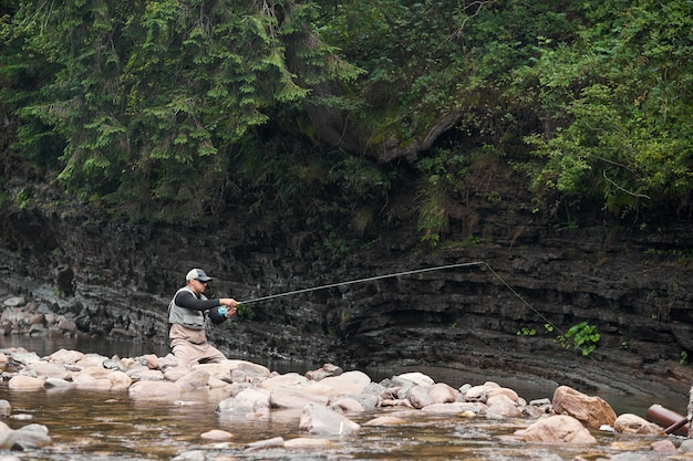 Молодой человек в униформе и кепке сидит на большом камне во время рыбалки на горной реке. профессиональный рыбак, наслаждаясь любимым хобби на свежем воздухе.