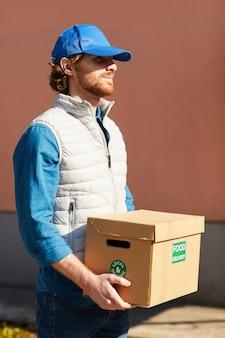 Молодой человек в форме, несущий картонную коробку с едой на открытом воздухе, доставляет еду