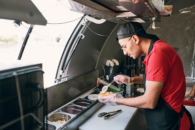 フードトラックでおいしいホットドッグを均一に調理する若い男