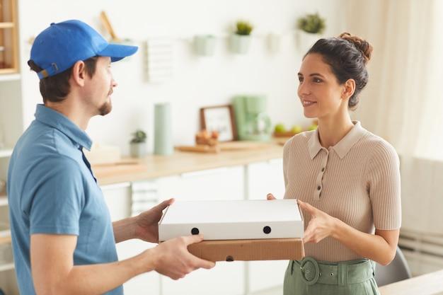 Молодой человек в униформе доставляет пиццу молодой женщине дома