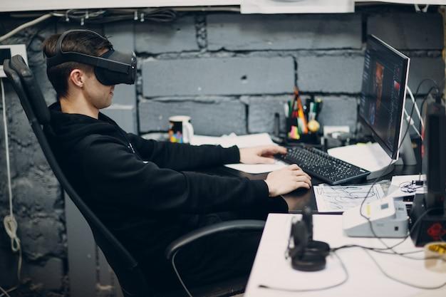 仮想現実の若い男ゴーグル、コンピューターに座ってvrメガネヘッドセット