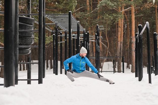 ウィンタースポーツグラウンドで運動しながらしゃがみ内転筋ストレッチをしている暖かい服を着た若い男
