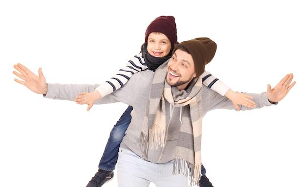 Молодой человек в теплой одежде, играя с сыном на белом фоне. готовы к зимнему отдыху