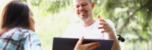 휠체어를 탄 젊은 남자와 공원에서 노트북 화면을 보고 있는 여자