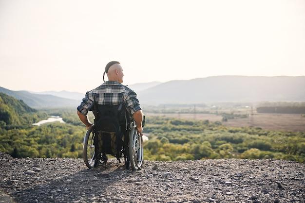 山で晴れた日に新鮮な空気を楽しんでいる車椅子の若い男