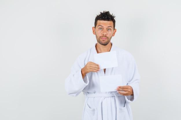 Молодой человек в белом халате, холдинг чистые листы бумаги, вид спереди.