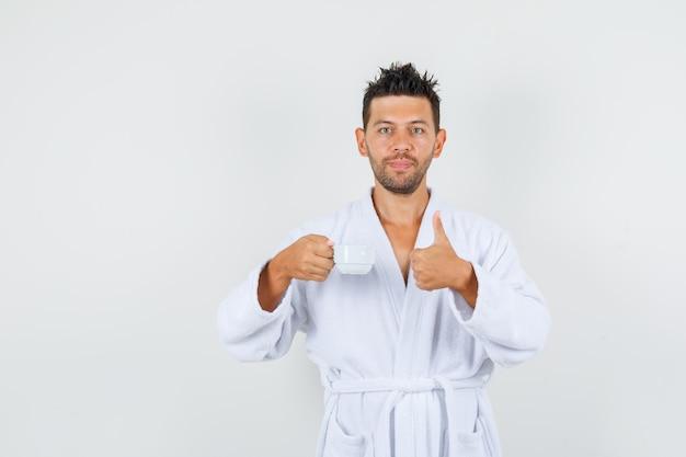 Молодой человек в белом халате держит чашку кофе с большим пальцем вверх и выглядит довольным, вид спереди.