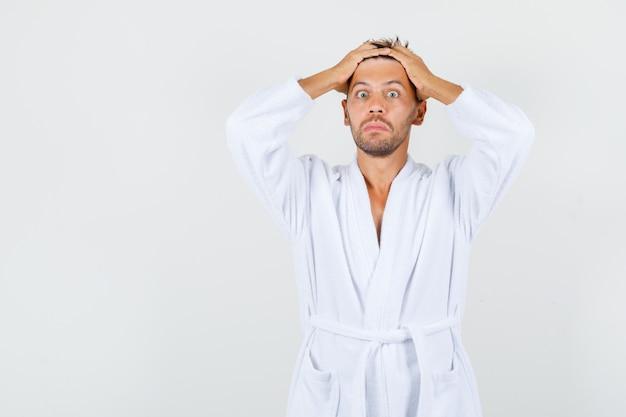 頭に手をつないで、驚いて見える白いバスローブを着た若い男、正面図。