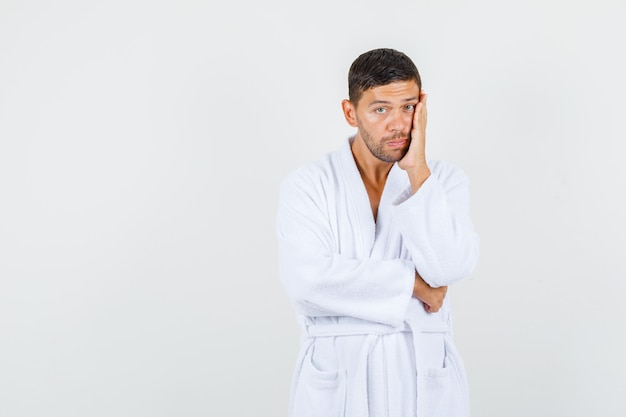 白いバスローブを着た若い男が頬に手のひらを持って物思いにふける、正面図。