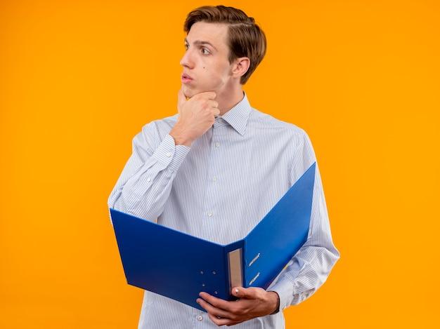 オレンジ色の背景の上に立って自信を持って見えるあごに手で脇を見てフォルダーを保持している白いシャツの若い男