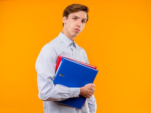 オレンジ色の背景の上に立っている深刻な顔とカメラを見てフォルダーを保持している白いシャツの若い男