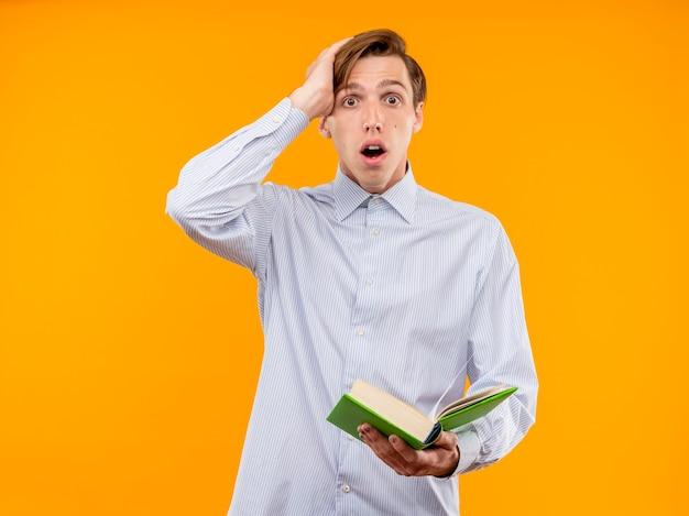 Молодой человек в белой рубашке держит открытую книгу, глядя в камеру, смущенный и удивленный, стоя на оранжевом фоне