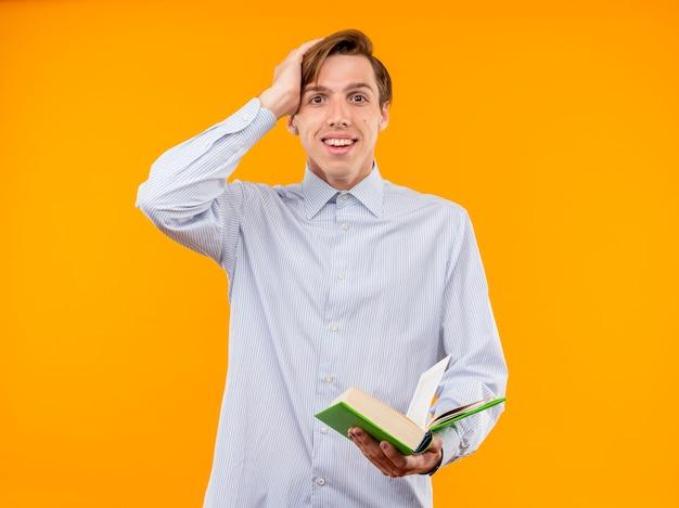 Молодой человек в белой рубашке держит открытую книгу, весело улыбаясь, удивленный, стоя у оранжевой стены