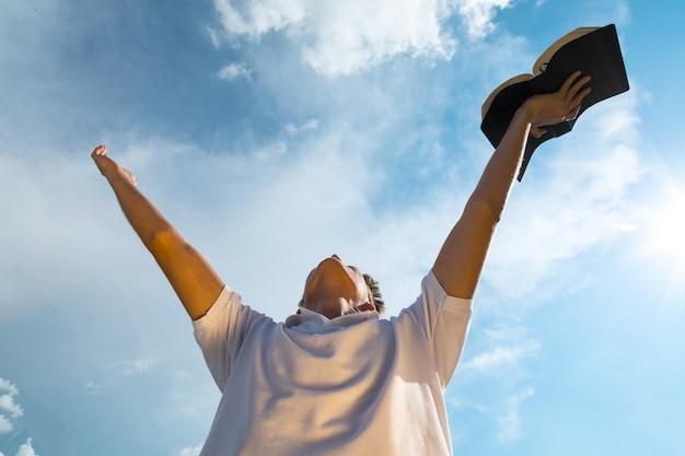 青い空の背景に開いた本を保持している白いシャツの若い男