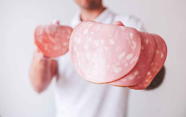 Молодой человек в белой рубашке, изолированных вырезать вид парня, держа в руках ломтики ветчины. вкусный вкусный кусочек колбасы.