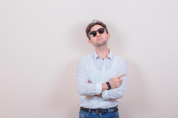 흰 셔츠에 젊은 남자, 옆으로 가리키는 청바지, 안경을 통해 찾고