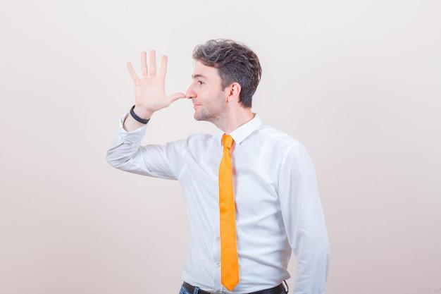 Молодой человек в белой рубашке, джинсах касается носа большим пальцем и выглядит забавно