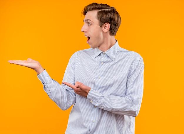 オレンジ色の背景の上に立っている何かに人差し指で指している彼の手の腕で何かを提示して驚いて幸せな脇を見て白いシャツを着た若い男