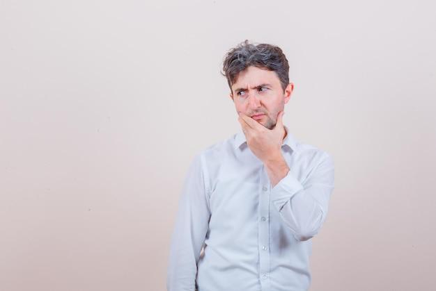 Молодой человек в белой рубашке смотрит в сторону, положив руку на подбородок и выглядит задумчивым